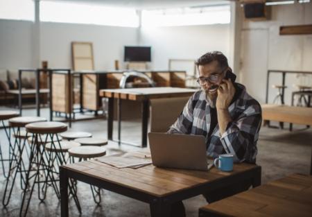 mężczyzna siedzący przy stole przed komputerem izrozmawiający przez telefon